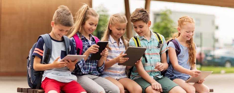 Eine Gruppe Schüler sitzt beisammen, jeder hält ein Smartphone oder Tablet in der Hand, sie lächeln.