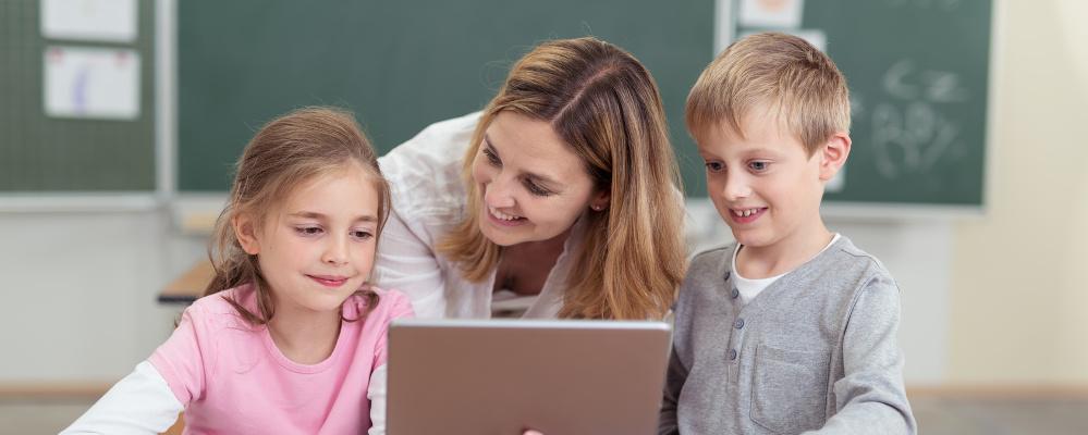 Frau erklärt Kindern Tablet